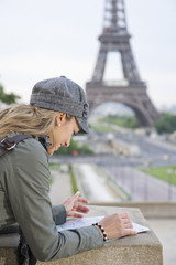 Hispanic woman looking at map near the Eiffel Tower