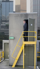 Caucasian businessman standing on city rooftop