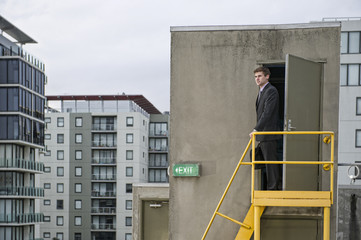 Caucasian businessman standing on rooftop