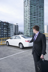 Caucasian businessman locking his car in parking lot