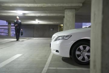 Caucasian businessman walking in parking garage