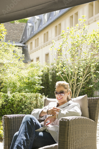 Hispanic woman relaxing in armchair outdoors