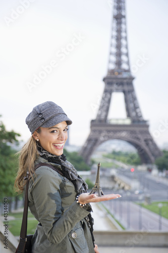 Hispanic woman holding a souvenir Eiffel Tower near the actual Eiffel Tower