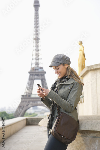 Hispanic woman using cell phone near the Eiffel Tower