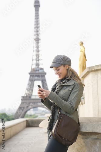 Hispanic woman using cell phone near the Eiffel Tower