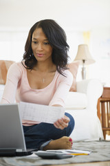 African American woman paying bills online