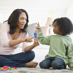 African American mother teaching son numbers