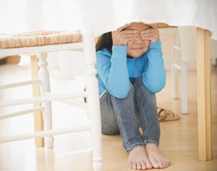 Korean girl hiding underneath table
