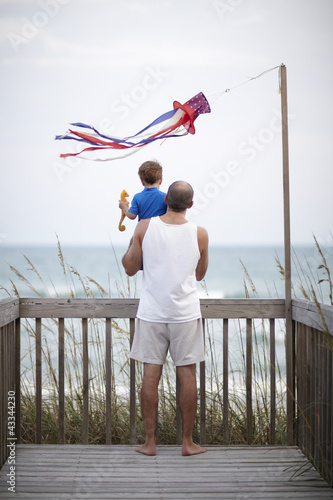 Father holding son on deck near ocean
