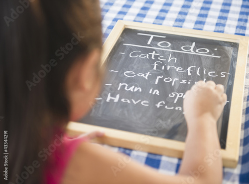 Korean girl writing to do list on blackboard