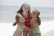 Caucasian girls hugging on beach