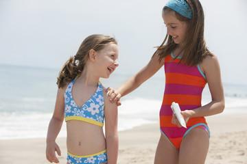 Caucasian girl putting sunscreen on sister