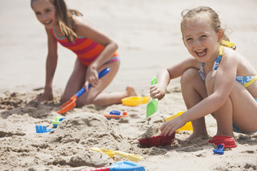 Caucasian girls playing in sand