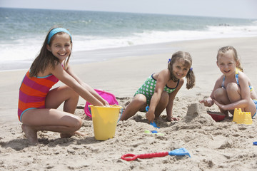 Caucasian girls playing in sand