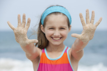 Caucasian girl on the beach with sandy hands