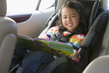 Caucasian girl sitting in car seat with book