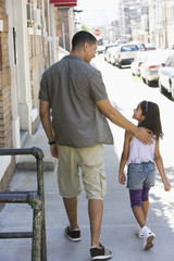 Father and daughter walking on sidewalk