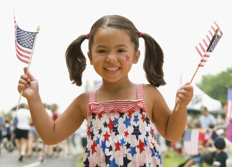 Caucasian girl waving American flags