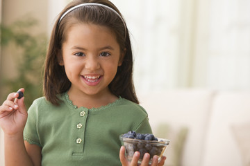 Caucasian girl eating blueberries