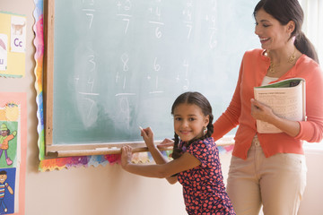 Teacher helping student at blackboard in classroom