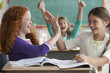 Students high-fiving in classroom