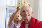 Caucasian girl putting crown on grandfather's head