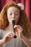 Mixed race girl playing recorder