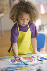 Mixed race boy painting picture