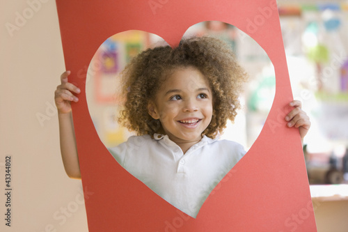 Grinning mixed race boy looking through heart-shaped hole