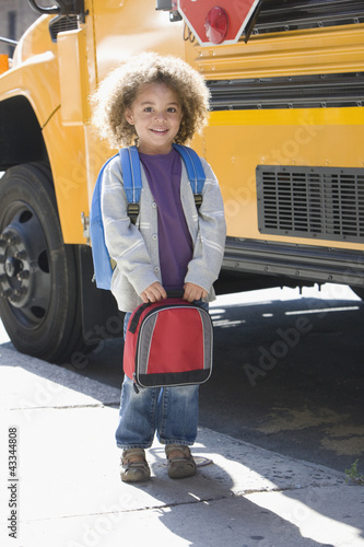 Mixed race boy standing near school bus