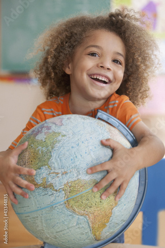 Mixed race boy holding globe
