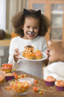 Mixed race girl in Halloween costume decorating cupcakes