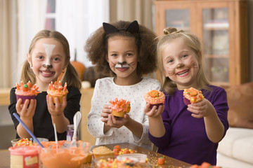 Girls in Halloween costumes decorating cupcakes
