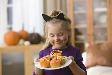 Caucasian girl in Halloween costume holding cupcakes