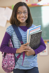 Hispanic girl holding books in classroom