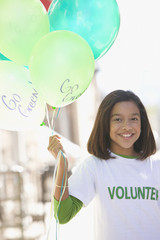 Hispanic girl volunteering and holding balloons