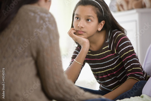 Mother talking to daughter in bedroom