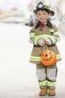 Caucasian boy dressed in fireman Halloween costume