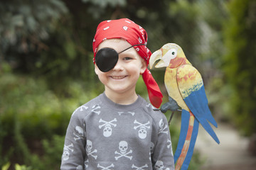 Caucasian boy dressed as pirate with parrot on shoulder