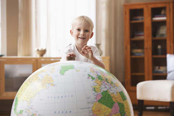 Caucasian boy playing with large globe