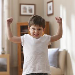 Caucasian boy flexing muscles
