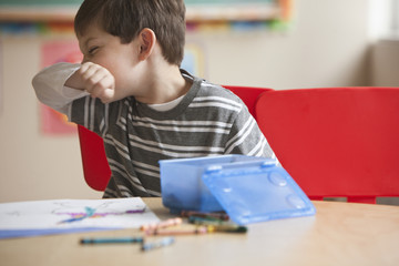 Caucasian boy blowing nose in classroom