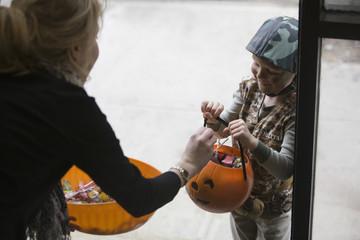 Caucasian boy trick or treating on Halloween