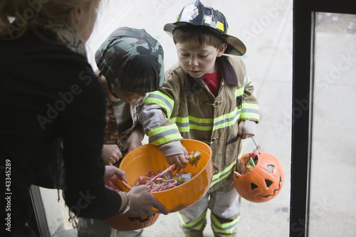Caucasian boys trick or treating on Halloween