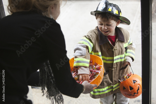 Caucasian boy trick or treating on Halloween