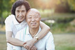 Smiling senior Chinese couple hugging