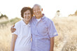 Smiling senior Chinese couple standing in field