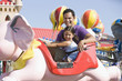 Hispanic father and daughter riding amusement park ride