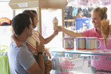 Waitress handing ice cream cone to young girl