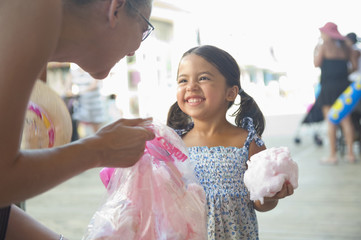 Hispanic mother handing cotton candy to daughter